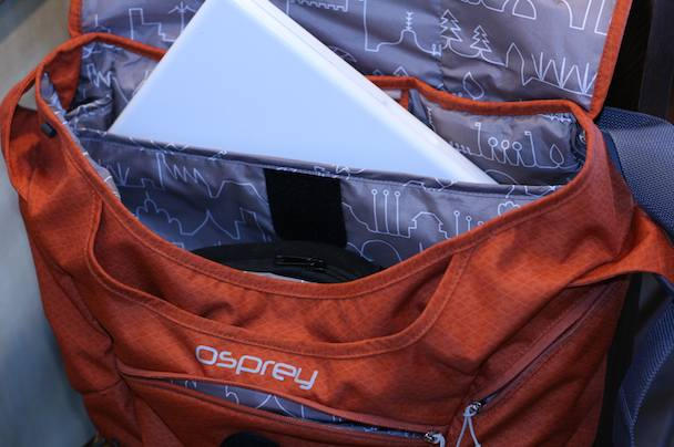 "The bag's padded laptop sleeve comfortably swallows a 15"" MBP (13"" Macbook in the photo, though) and is suspended above the bag's bottom."
