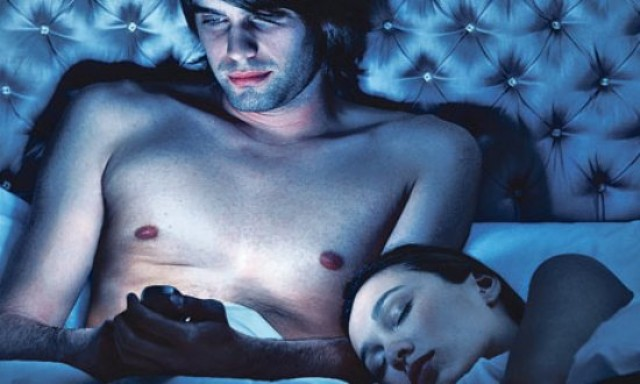 man-using-iphone-in-bed