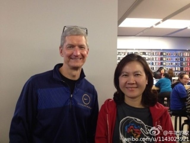 Apple CEO Tim Cook poses with fan at the company's Xidan Joy City store in Beijing.