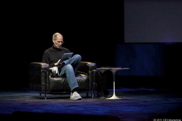 Steve Jobs reclines in a chair on stage to show off the iPad.