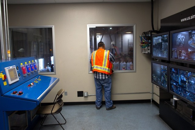 Robert Fragoso, Sims' operations supervisor, looks out a window at the warehouse floor. Monitors on the wall show how things are going on the shredder line. Photo: Jim Merithew/Cult of Mac