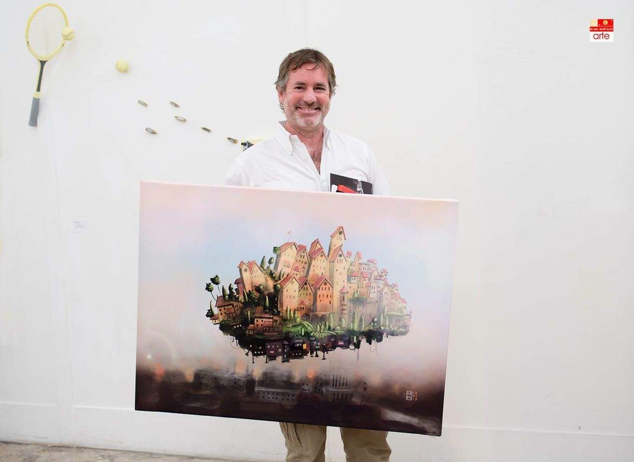 Watkins holds a fingerpainting titled  It's a long way up featured at an exhibit in Verona, Italy.