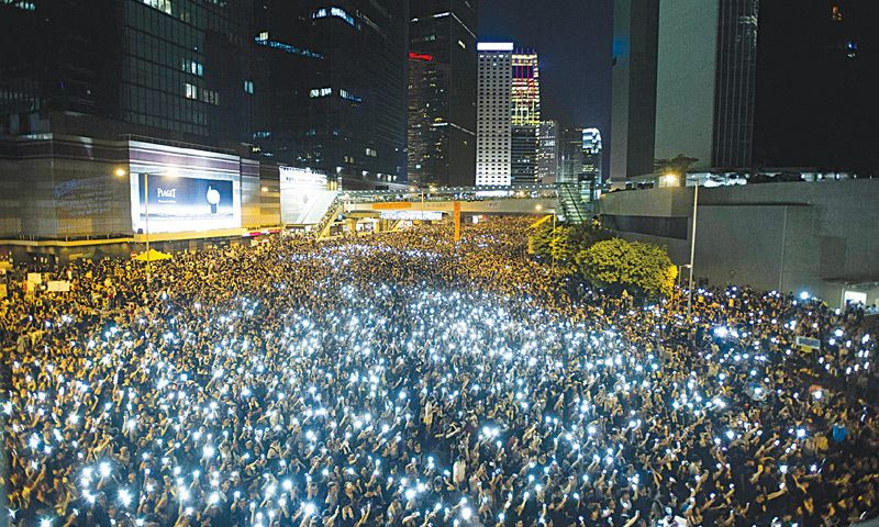 Protesters in Hong Kong hold their phones high. Photo: AFP