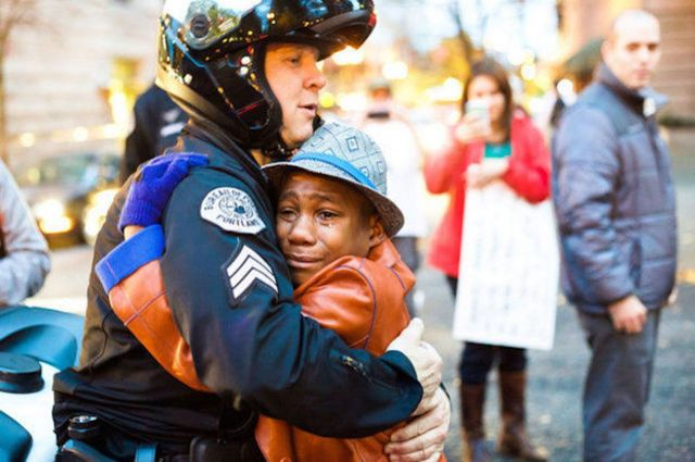 Nov. 25: Portland police Sgt. Bret Barnum, left, and Devonte Hart, 12, hug at a rally in Portland, Ore., where people had gathered in support of the protests in Ferguson, Mo. (Johnny Huu Nguyen/Associated Press)