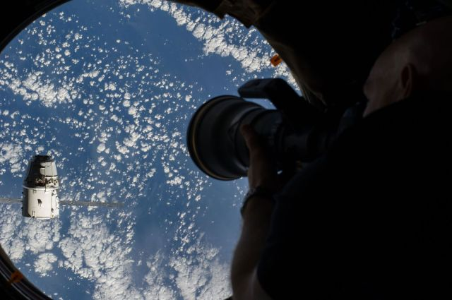 European Space Agency astronaut Alexander Gerst, Expedition 41 flight engineer, uses a still camera at a window in the Cupola of the International Space Station as the SpaceX Dragon commercial cargo craft approaches the International Space Station on Sept. 23. Photo: NASA