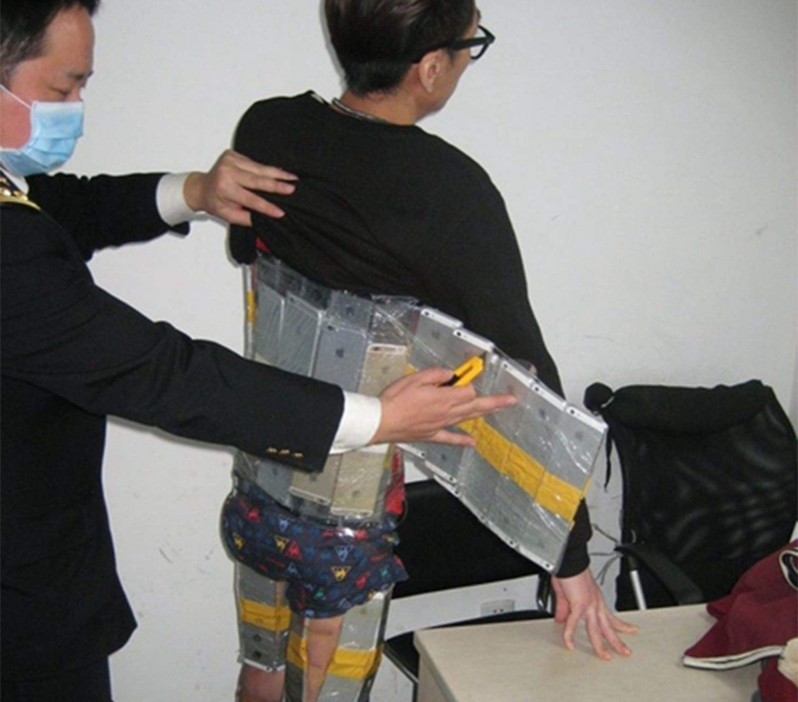 Customs officials in China caught this man trying to smuggle 94 iPhones into the country. Photo: Sina News