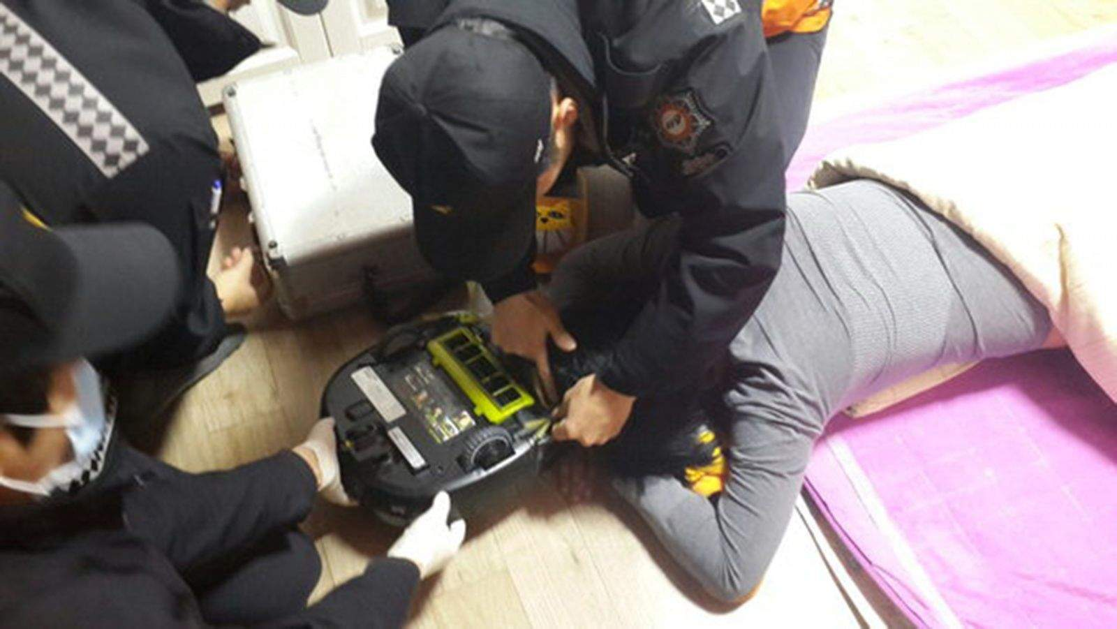 Paramedics work to free a woman from the grips of her robot vacuum. Photo: Changwon Fire Service