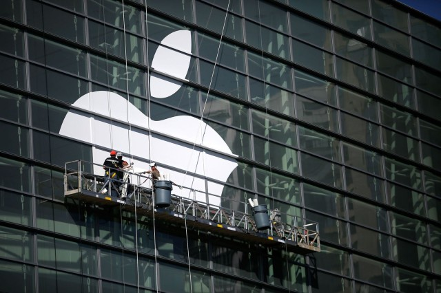 Workers apply a massive Apple logo to Moscone Center's glass wall.