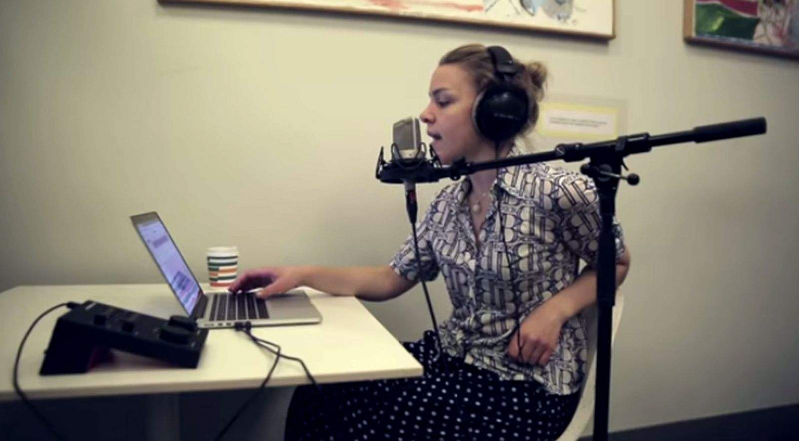 A singer records vocals using Sountrap recording software, which can be used on any device.