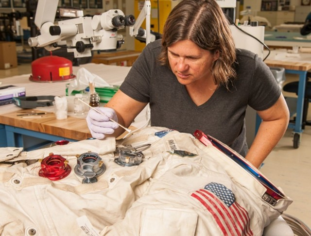 Conservator Lisa Young works on the Armstrong suit.