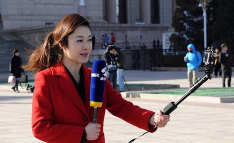 This reporter's microphone windscreen is bulkier than the iPhone she is using to broadcast live.