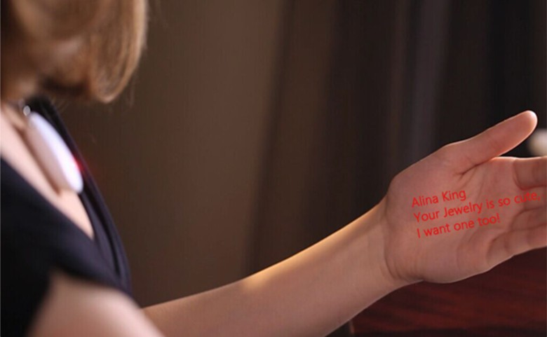 The wearer can read text messages on their hand that come from a micro projector located in the pendant.