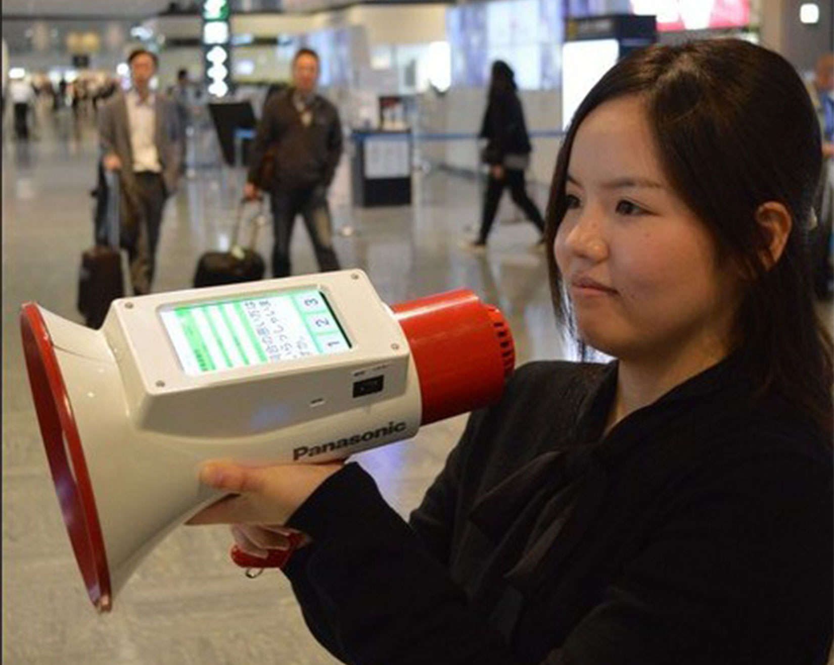 An airport worker holds the Megaphoneyaku, which can broadcast messages in three languages.
