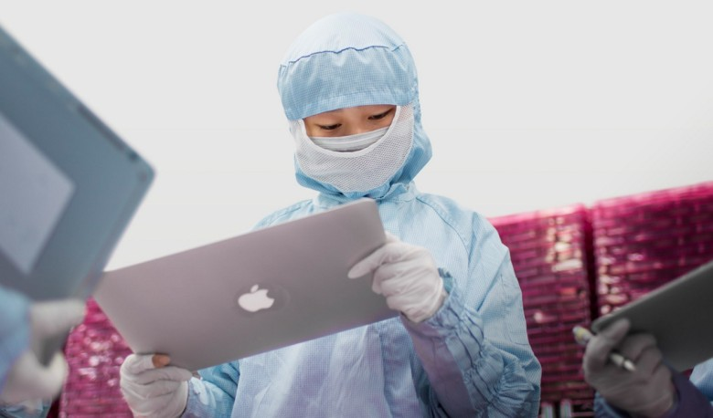 A worker inspecting a MacBook Pro display.