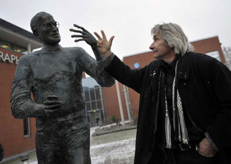 Artist Tóth Ernö, right, gestures with his bronze creation of Jobs.