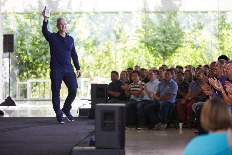 Tim Cook holds Apple's billionth iPhone.