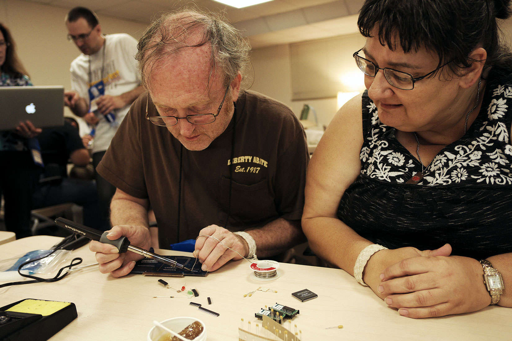 Rachele Lane watches her husband, John, try his hand at soldering at KansasFest.