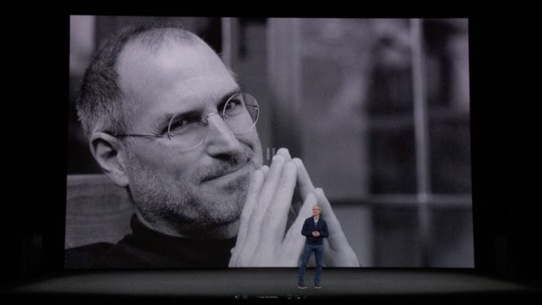 With a photo of Steve Jobs in the background, Tim Cook talks about Apple's goal to