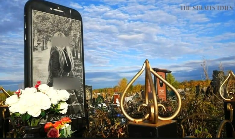 The iPhone gravestone stands tall in a Russian cemetery.