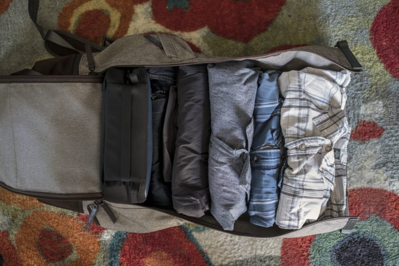 Inside is a cord-organizing case, jeans, shorts and three shirts. Socks and underwear hidden behind