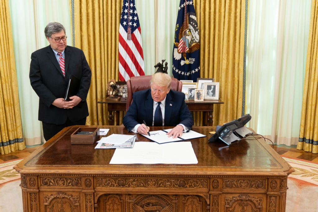 President Trump signs the executive order.